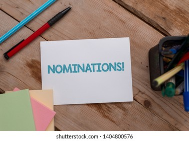 Conceptual hand writing showing Nominations. Business photo showcasing action of nominating or state being nominated for prize Note papers and stationary placed sideways softhued backdrop.