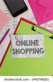 Conceptual hand writing showing Online Shopping. Business photo showcasing allows consumers to buy their goods over the Internet Clipboard sheet pencil smartphone clips notepad wooden back.