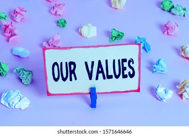 Conceptual hand writing showing Our Values. Business photo text list of morals companies or individuals commit to do them Colored crumpled papers empty reminder pink floor clothespin.