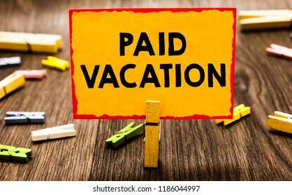 Conceptual hand writing showing Paid Vacation. Business photo showcasing Sabbatical Weekend Off Holiday Time Off Benefits Clothespin holding orange paper note clothespin wooden floor.