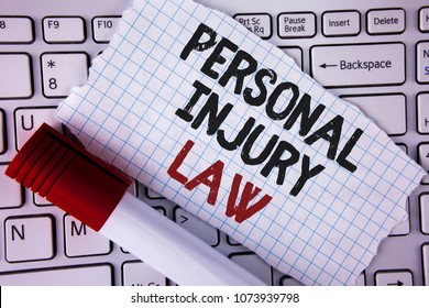 Conceptual hand writing showing Personal Injury Law. Business photo text guarantee your rights in case of hazards or risks written on Tear Notebook paper placed on the Laptop Marker next to it..