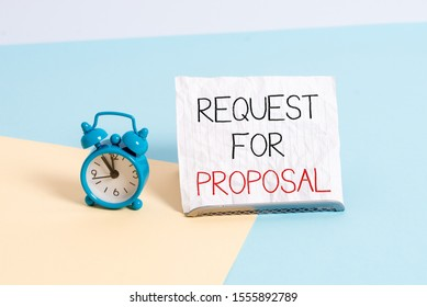 Conceptual hand writing showing Request For Proposal. Business photo text document contains bidding process by agency or company Alarm clock beside a Paper sheet placed on pastel backdrop.