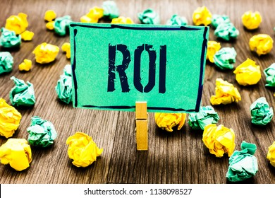 Conceptual hand writing showing Roi. Business photo showcasing Return on investment performance measure gains business growth Crumpled papers ideas mistakes paperclip clip objects wood.