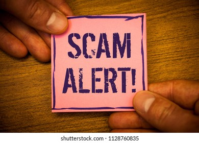 Conceptual hand writing showing Scam Alert Motivational Call. Business photos text Safety warning to avoid fraud or virus attacksMan hold holding pink note ideas black letters and wooden background
