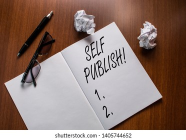 Conceptual hand writing showing Self Publish. Business photo text writer publish piece of ones work independently at own expense Notebook small wrinkled paper balls reading glasses wooden table.