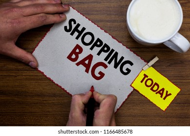 Conceptual hand writing showing Shopping Bag. Business photo text Containers for carrying personal possessions or purchases Man holding marker notebook reminder wooden table cup coffee.