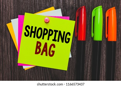 Conceptual hand writing showing Shopping Bag. Business photo showcasing Containers for carrying personal possessions or purchases Paper notes Communicate ideas Markers Wooden background.