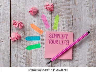 Conceptual hand writing showing Simplify Your Life. Business photo text focused on important and let someone else worry about less ones Note paper and line arrow stickers on the top of wooden table