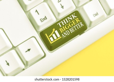 Conceptual hand writing showing Think Bigger And Better. Business photo text no Limits be Open minded Positivity Big Picture White pc keyboard with note paper above the white background.