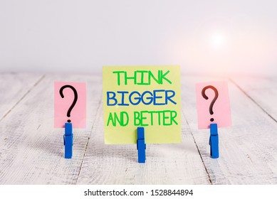 Conceptual hand writing showing Think Bigger And Better. Business photo text no Limits be Open minded Positivity Big Picture Crumbling sheet with paper clips placed on the wooden table.