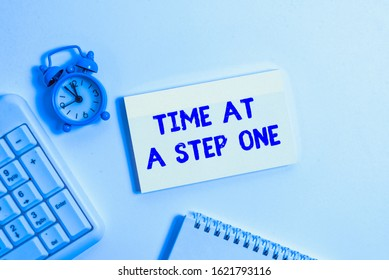 Conceptual hand writing showing Time At A Step One. Business photo text Slowly but Surely Milestone Careful Gradual Steps Keyboard with empty note paper and pencil white background.