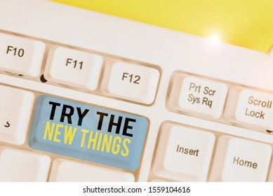 Conceptual hand writing showing Try The New Things. Business photo showcasing Breaks up Life Routine Learn some Innovative Skills White pc keyboard with note paper above the white background.
