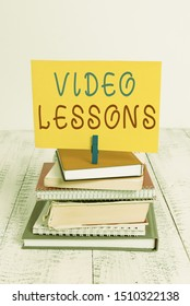 Conceptual hand writing showing Video Lessons. Business photo showcasing Online Education material for a topic Viewing and learning pile stacked books notebook pin color reminder white wooden.