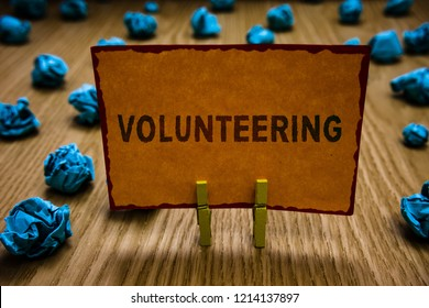 Conceptual hand writing showing Volunteering. Business photo text Provide services for no financial gain Willingly Oblige Clothespins holding orange paper note crumpled papers mistake.