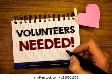 Conceptual hand writing showing Volunteers Needed Motivational Call. Business photo text Social Community Charity Volunteerism Human hand retain black pen notepad with words on paper pink heart.