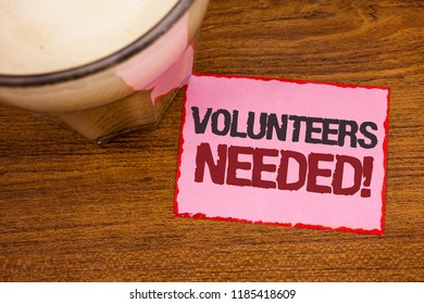 Conceptual hand writing showing Volunteers Needed Motivational Call. Business photo text Social Community Charity Volunteerism Wooden desktop red lined pink paper with several texts coffee mug.