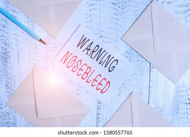 Conceptual hand writing showing Warning Nosebleed. Business photo text caution on bleeding from the blood vessels in the nose Envelopes highlighter ruled paper sheet wooden vintage background.