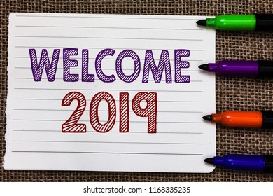 Conceptual hand writing showing Welcome 2019. Business photo showcasing New Year Celebration Motivation to Start Cheers Congratulations Notebook Paper Important reminder Markers Jute background.