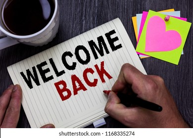 Conceptual hand writing showing Welcome Back. Business photo text Warm Greetings Arrived Repeat Gladly Accepted Pleased Man holding marker giving ideas wooden table cup coffee hearts.
