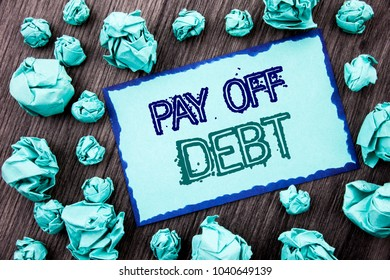 Conceptual hand writing text showing Pay Off Debt. Concept meaning Reminder To Paying Owed Financial Credit Loan Bills written Sticky note paper folded paper the wooden background.