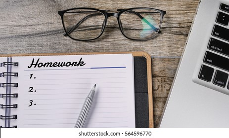 Conceptual of homework written on wooden table with notebook and spectacle