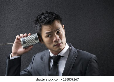Conceptual image is about communication. Chinese Business man Listening to a Tin Can Phone. Asian Business man with Tin Can Phone. Concept about communication.