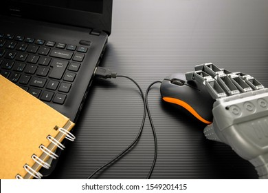 Conceptual image of artificial intelligence. Robotic hand handling computer mouse of a black notebook on glossy dark surface. Spiral yellow note book in visibility. Focus of mouse scroll wheel.