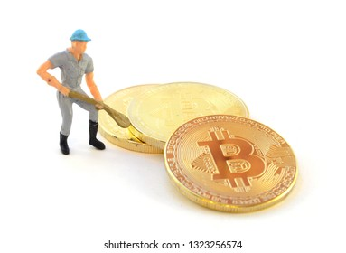 Conceptual image based on mining for digital currency using Bitcoin and a small figurine.