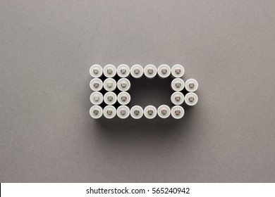 conceptual image of battery charge level pictogram made of rechargeable batteries over gray background
