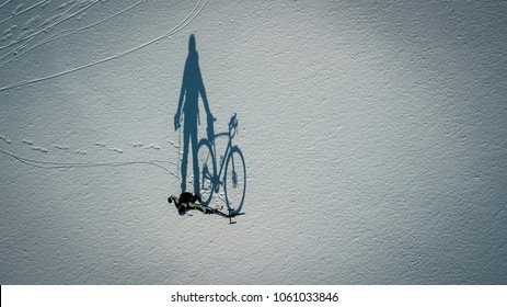 Conceptual image of bicyclist standing near by bike on the lake covered with ice and snow isolated on white, top view from drone. Huge shadow is seen on the snow.