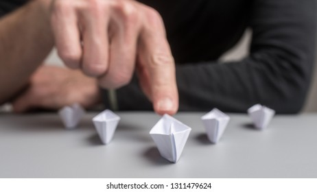 Conceptual image of business leadership and uniqueness - businessman pushing forward of of the five origami paper made boats.