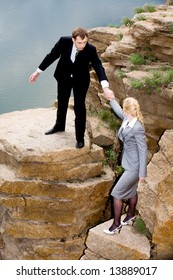 Conceptual image of business man helping to climb to mountain to his colleague