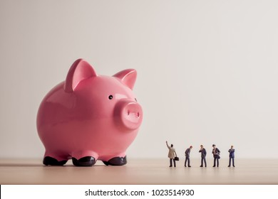 Conceptual image of business people looking at giant Piggy Bank.