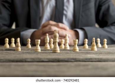 Conceptual image of business vision with a man wearing suit sitting in front of white chess pieces at table.