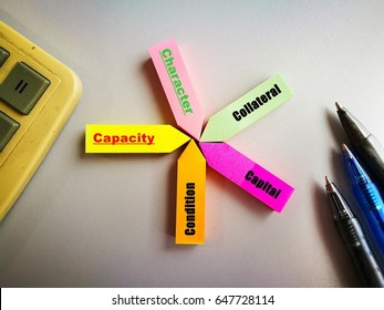 "conceptual image of business/finance. Words ""capacity, character, capital, condition, collateral"" on colorful sticky notes. On white surface with calculator and pens. Natural light source from window."