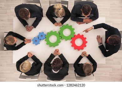 Conceptual image of businessteam working cohesively , colorful cogs on table, interaction and unity