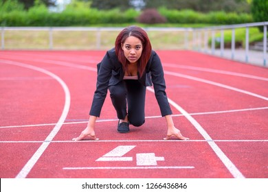 Conceptual image of a businesswoman on a race track in the ready position on the starting line facing towards the camera