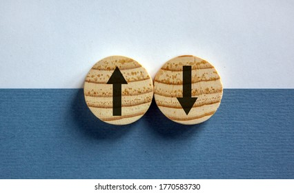 Conceptual image of choice and direction. Wooden circles with arrows pointing in opposite directions. Beautiful white and blue background, copy space.
