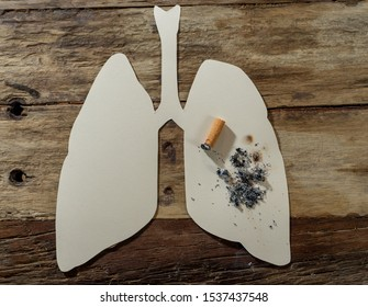 Conceptual image of cigarette burning on paper lungs isolated on rustic background. Advertising style of Tobacco and lung cancer, Medical warning, stop smoking and smoking kills campaign.