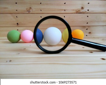 Conceptual image. Colourful ping pong ball on wooden pallet. There are racist on colour. Focus on white.