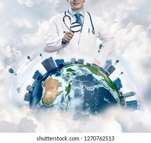 Conceptual image of confident doctor in white medical uniform looking on the Earth globe through loupe with cloudy skyscape on background. Medical industry concept. Elements of this image furnished by