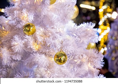 Conceptual image of decorated outdoor white Christmas tree with colorful lights and ornaments