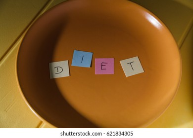 Conceptual image for dieting: plate with colour paper pieces spelling the word diet.