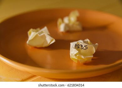 Conceptual image for dieting: plate with paper pieces spelling carbs.