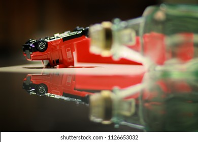 Conceptual image of drink don't drive.Image of overturned truck, toy truck was overturned with empty whisky bottle laid in foreground.The represent of A drunk driving accident.