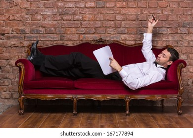 Conceptual image of an elegant businessman lying relaxing on a settee against a brick wall and reading paperwork