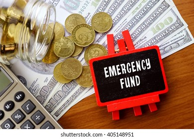Conceptual image with EMERGENCY FUND words. Hundred dollar bills, coins and calculator on wooden background.