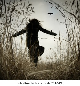 Conceptual image of a female person running with a raven.