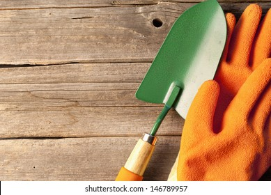 Conceptual image of gardening equipment consisting of gloves, clay flowerpots and a small trowel and fork lying on rustic wooden boards with copyspace above