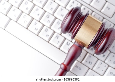 Conceptual image of a gavel used by a judge or auctioneer with a brass band around the head lying on a computer keyboard